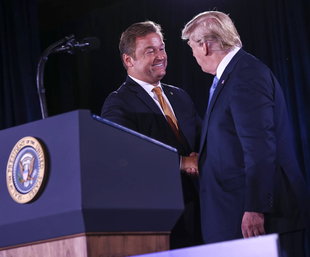 Chase Stevens/Las Vegas Review-Journal President Donald Trump greets U.S. Sen. Dean Heller, R-Nev., during the keynote address at the Nevada Republican Party State Convention at the Suncoast in L ...