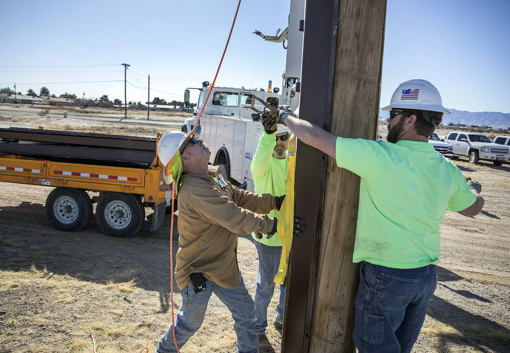 Valley Electric Association From left, Butch Davies and Cory Parker, both journeymen linemen, and Apprentice Lineman Schain Thomson, center, work to reinforce an existing VEA power pole.
