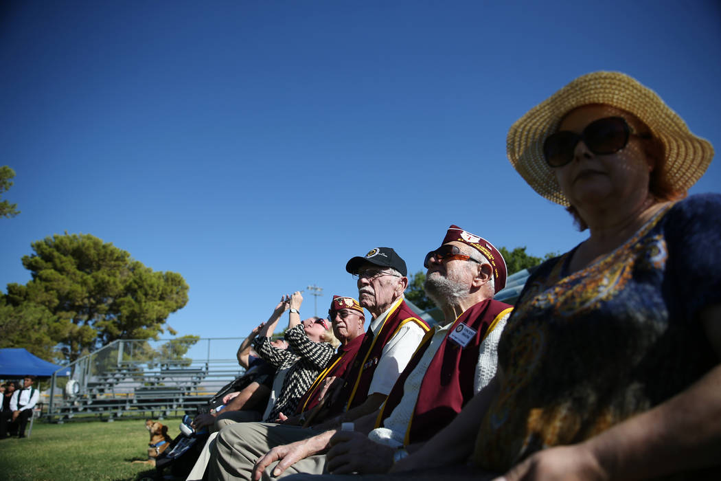 Military prisoners of war from left, Gene Ramos, Dean Whitaker, and Vincent Shank with his daughter Nancy, watch a flyover by three F-16 Fighting Falcons during a POW/MIA Recognition Day ceremony ...
