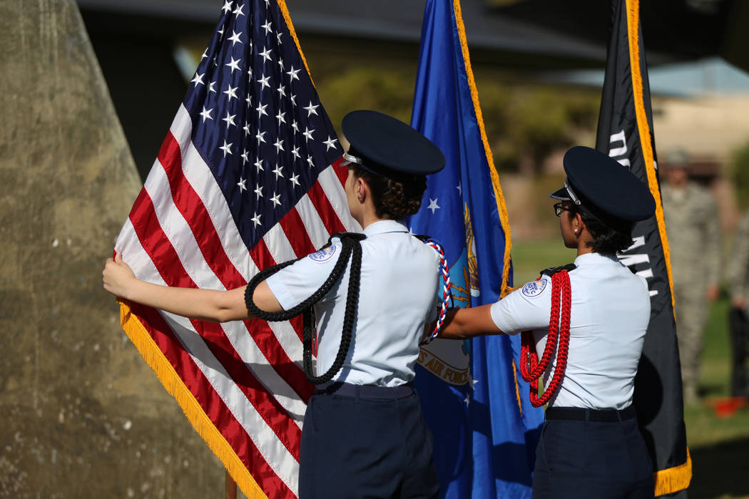 Rancho High School's JROTC color guard members Stephanie Morales, left, and Katelyn Dubro, present the colors during a POW/MIA Recognition Day ceremony at Freedom Park inside Nellis Air Force Base ...
