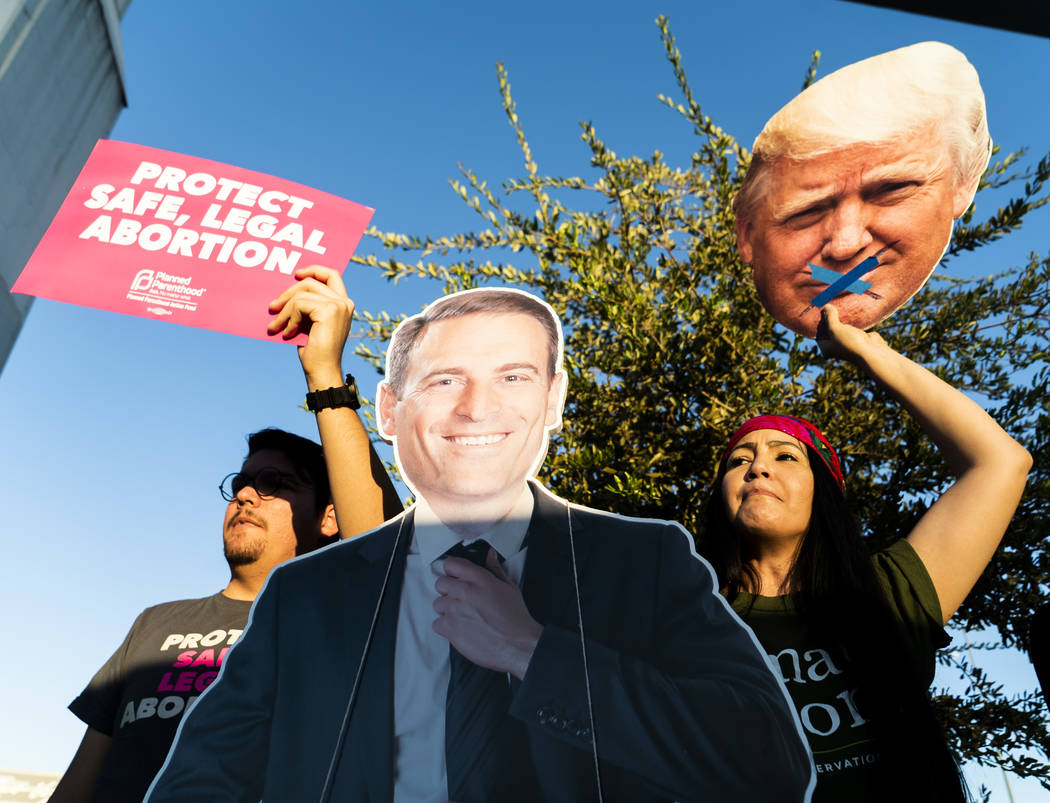 Alex Camberos, left, and Barbara Hartzell protest against President Donald Trump in front of the Las Vegas Convention Center in Las Vegas, Thursday, Sept. 20, 2018. (Marcus Villagran/Las Vegas Rev ...
