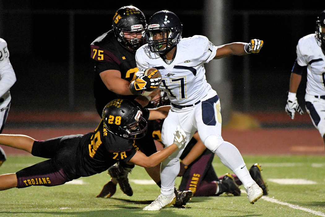 Peter Davis/Special to the Pahrump Valley Times Pahrump Valley seniors Zach Trieb (75) and Dylan Grossell (28) combine to stop Cheyenne's sophomore running back Majae Madison during Friday night's ...