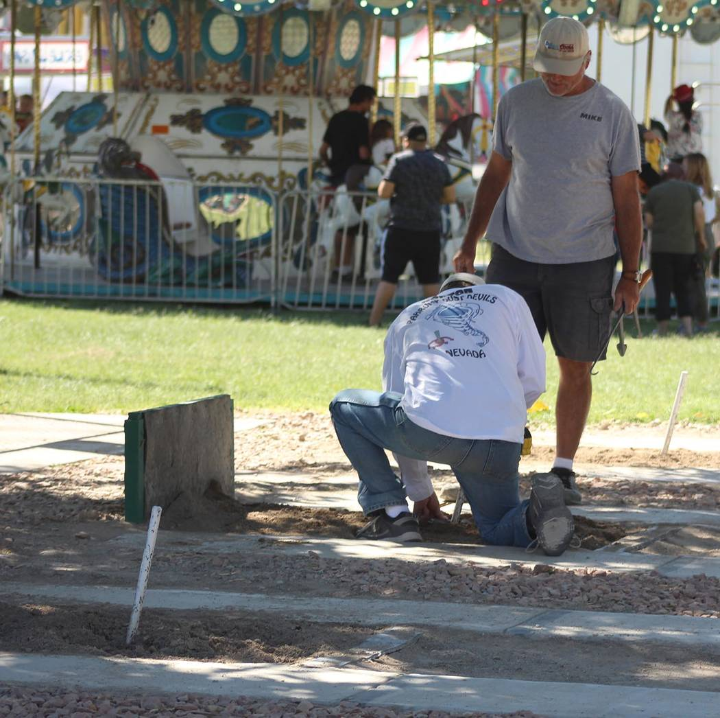 Tom Rysinski/Pahrump Valley Times Steve Nicosia watches as Mike Norton comes out to judge a horseshoe during the finals of the Pahrump Fall Festival tournament on Saturday at Petrack Park.