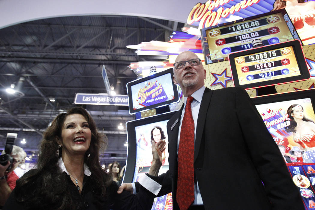 """Lynda Carter, left, star of the TV series """"Wonder Woman,"""" and Richard Haddrill, CEO at Bally Technologies, pose for photos at the unveiling of the Bally Wonder Woman slot machine during the Global ..."""