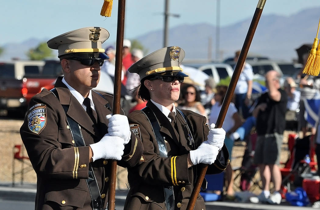 "Horace Langford Jr./Pahrump Valley Times Members of the Nye County Sheriff's Office Color Guard unit, a fixture at the fall festival parade, display the ""colors"" as they make their way along Highw ..."