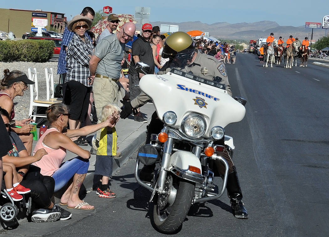 Horace Langford Jr./Pahrump Valley Times A Nye County Sheriff's Office motorcycle patrol deputy takes time to greet a young fan along the parade route, much to the delight of the boys parents and ...