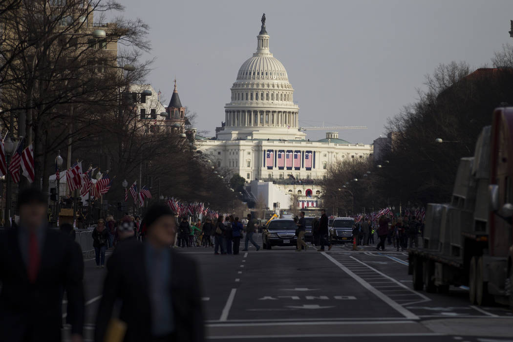 People walk on Pennsylvania Avenue near the U.S. Capitol and along the scheduled presidential inauguration parade route on Thursday, Jan. 19, 2017, in Washington. (Erik Verduzco/Las Vegas Review-J ...