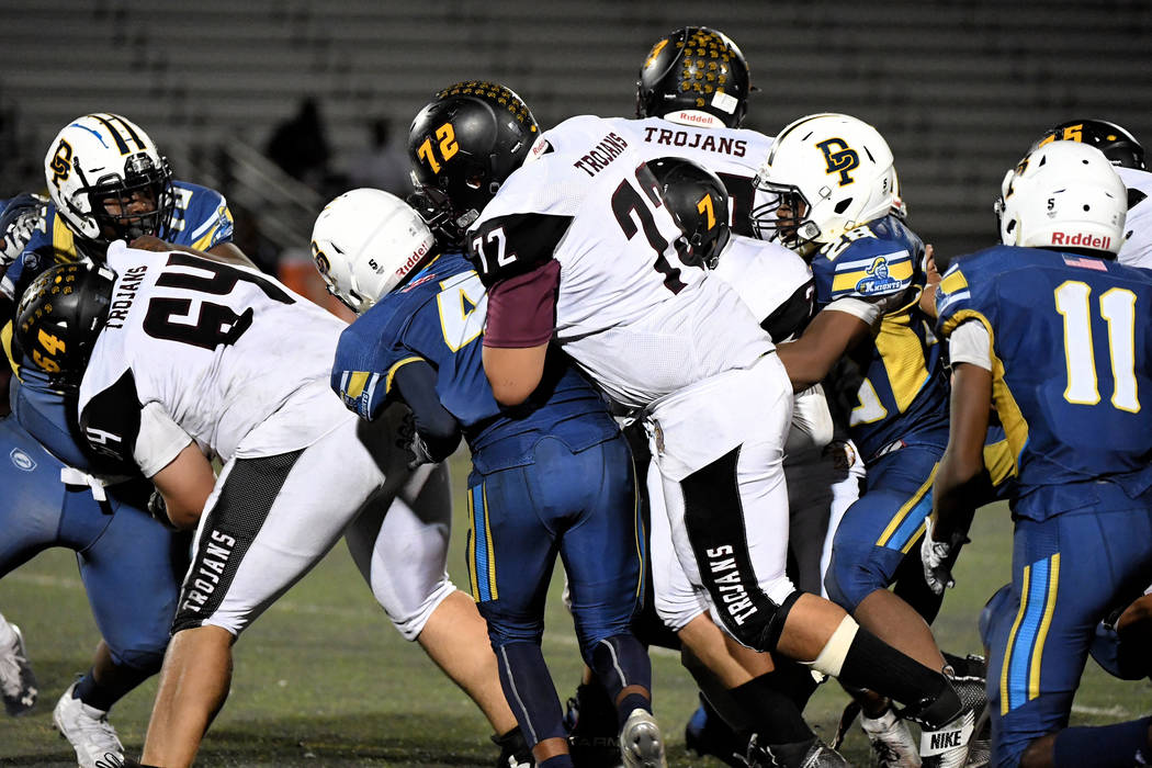 Peter Davis/Special to the Pahrump Valley Times Center Jakob Landis (64) and guard Caleb Sproul (72) open a path for quarterback Dylan Wright (7) to run through against Democracy Prep. Wright ran ...
