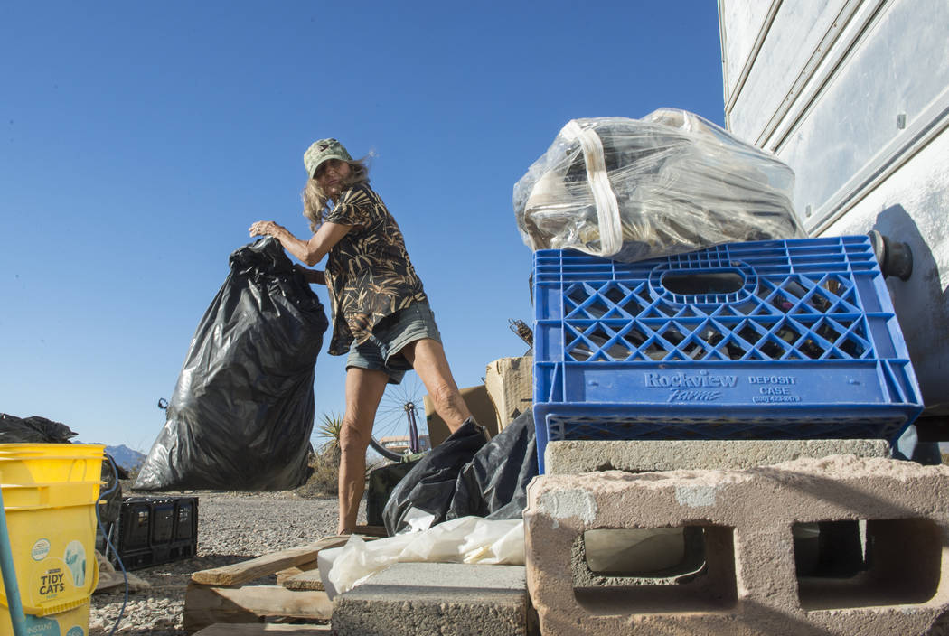 Homeless resident Mary Supples packs up her belongings laying outside of her trailer in preparation of moving her trailer to a third location within two weeks in Pahrump, Wednesday, Sept. 26, 2018 ...