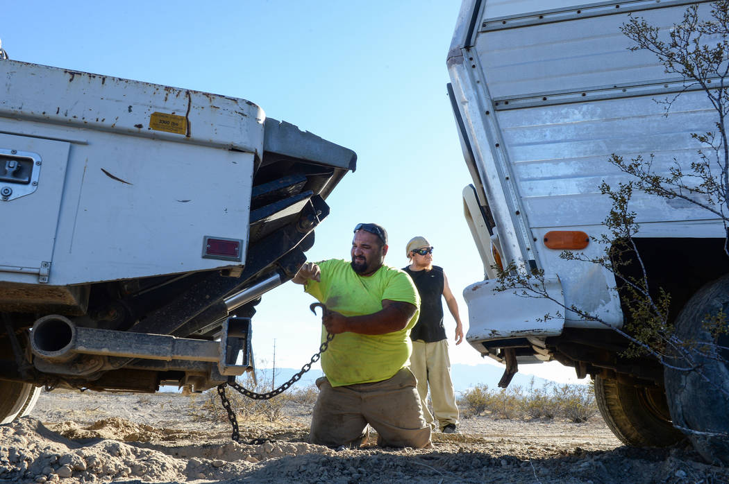 Jon Olivas of Platinum Hauling unhooks the chain linking his truck to Mary Supples' trailer in order to pull the trailer from the other side after getting stuck in some bushes as homeless resident ...