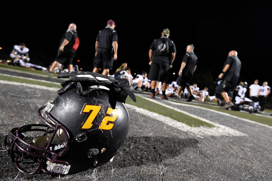 Peter Davis/Special to the Pahrump Valley Times Pahrump Valley senior lineman Caleb Sproul's helmet is a bystander as Trojans coaches address the team at halftime against Democracy Prep on Sept. 2 ...