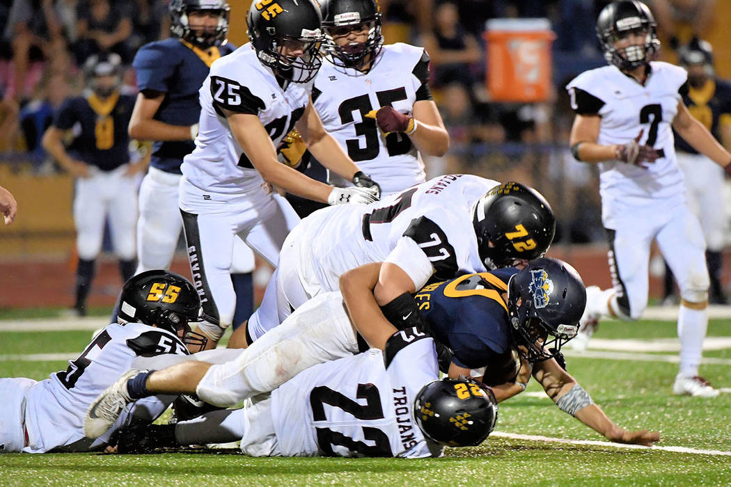 Peter Davis/Special to the Pahrump Valley Times Kody Peugh (55), Caleb Sproul (72) and Anthony Peralta (22) team up to make a tackle during a Sept. 7 game against Boulder City.