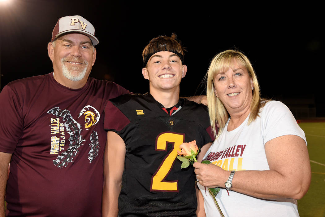Peter Davis/Special to the Pahrump Valley Times Trojans senior Joey Koenig with his parents during Senior Night festivities before Pahrump Valley's 66-0 win over Western on Friday night in Pahrump.