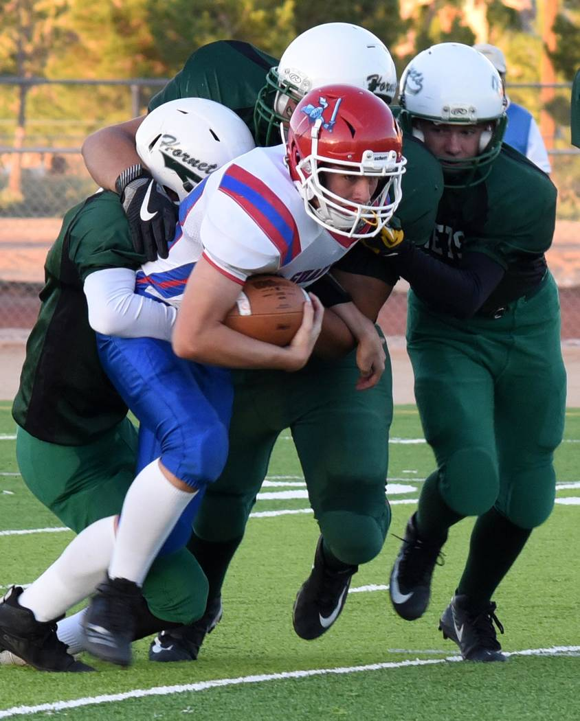 Richard Stephens/Special to the Pahrump Valley Times Three Beatty defensive players gang up on a Green Valley Christian ball carrier Sept. 27 in Beatty. The Hornets travel to Hawthorne tonight to ...