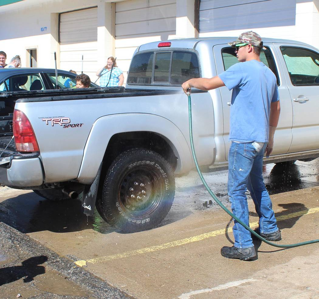 Tom Rysinski/Pahrump Valley Times Boy Scout Liam Mossey washes cars during a fundraiser Saturday across the street from the VFW post in Beatty.