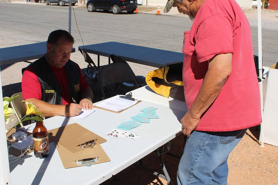 Tom Rysinski/Pahrump Valley Times Dan Sanders, left, commander of VFW Post #12108, checks in a participant selecting his poker hand Saturday during the fifth annual Poker Run in Beatty.