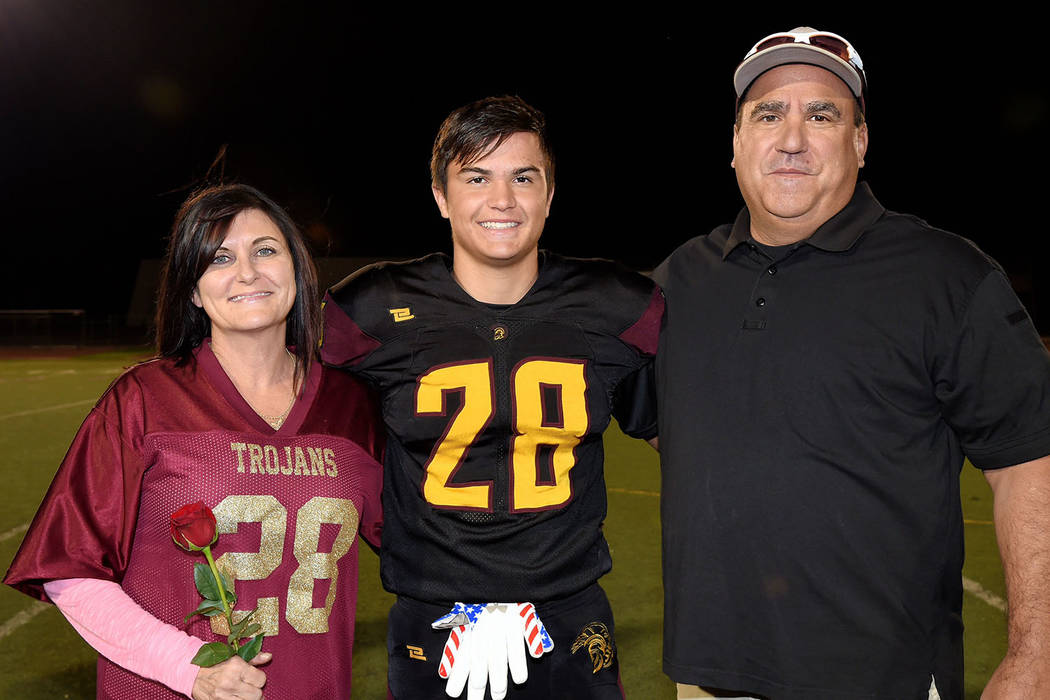 Peter Davis/Special to the Pahrump Valley Times Pahrump Valley senior tight end/linebacker Dylan Grossell with his parents on Senior Night on Oct. 12 at Trojan Field.