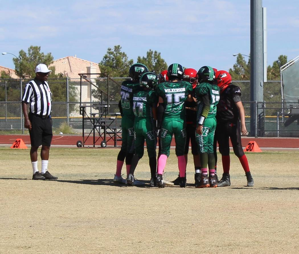 Tom Rysinski/Pahrump Valley Times Captains for the Pahrump Valley Warriors (green) and Southern Highlands Junior Rebels meet for the coin toss before their playoff game Saturday at Liberty High Sc ...