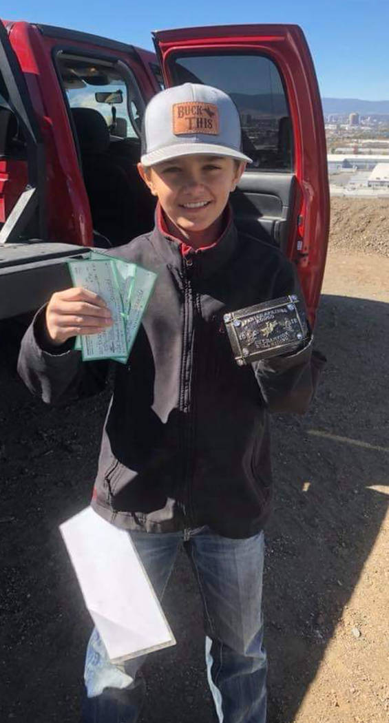 Buddy Krebs/Special to the Pahrump Valley Times Brandon Mountz of Pahrump shows off the checks and a buckle he won for his performances in bull riding and bareback steer riding at a junior high sc ...