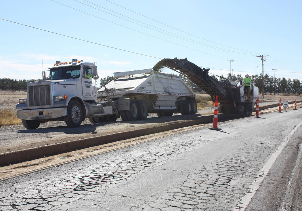 Robin Hebrock/Pahrump Valley Times Construction crews are seen grinding the existing road surface on Pahrump Valley Boulevard at East Mount Charleston Drive and loading the removed material into a ...