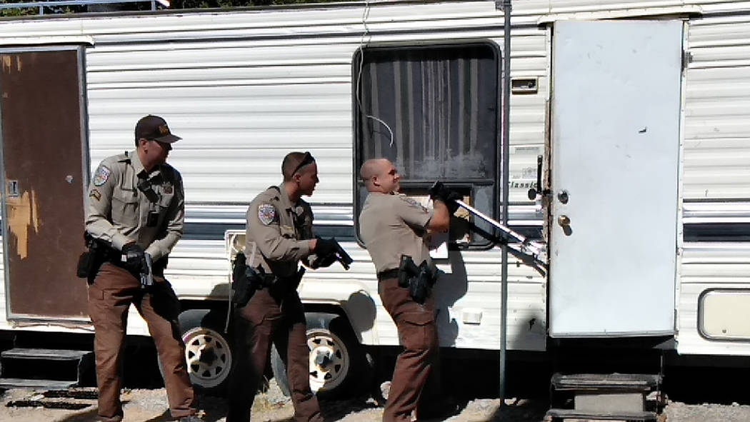 Selwyn Harris/Pahrump Valley Times Nye County Sheriff's Deputies with guns drawn, attempt to gain access to a trailer along the 600 block of East Street where a wanted suspect was believed to be r ...