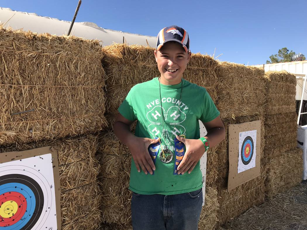 Jeffrey Meehan/Pahrump Valley Times Augustes Domina holds his two blue ribbons from the 2018 Nevada State 4-H Shooting Sports Match; he was also wearing his silver medal for his second-place win i ...