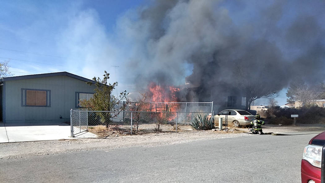 """Selwyn Harris/Pahrump Valley Times Pahrump Valley Fire and Rescue Service crews performed what's termed a """"blitz attack,"""" after arriving on scene. Several exposures including a nearby residence wa ..."""