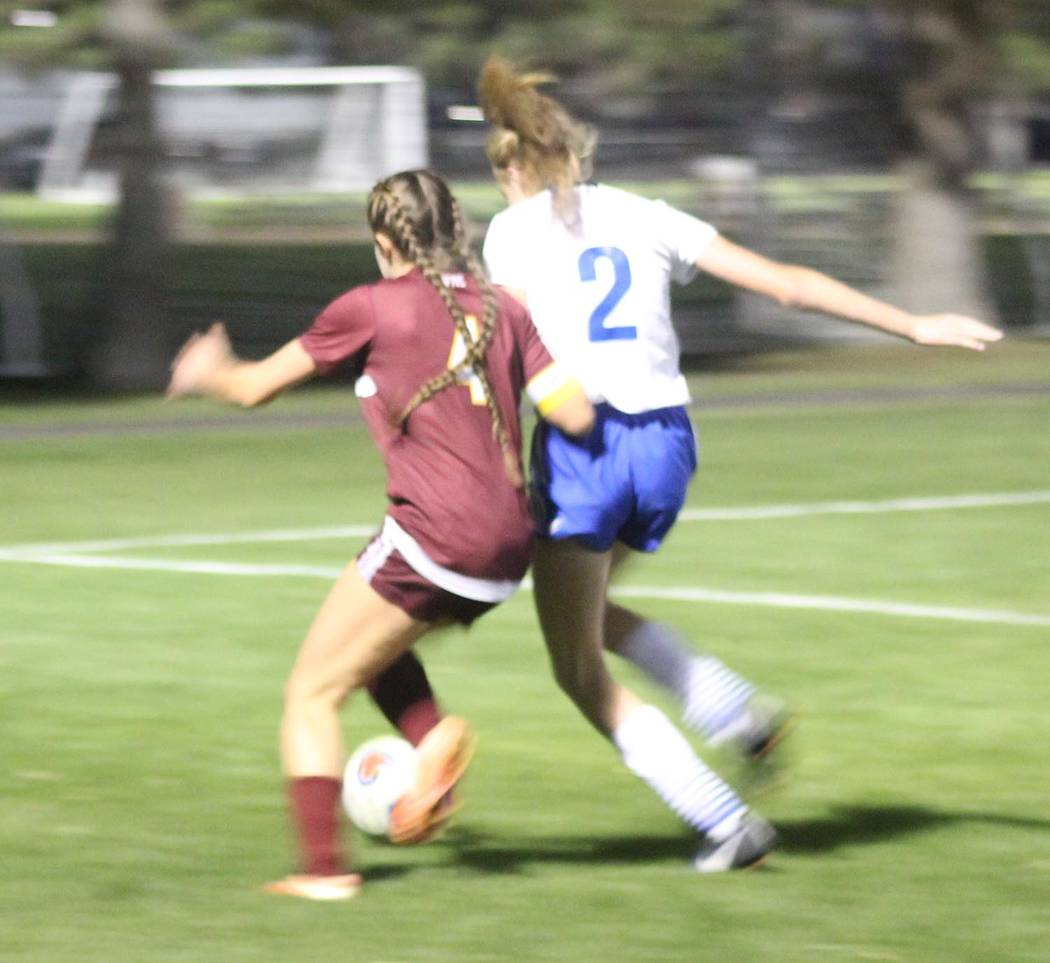Tom Rysinski/Pahrump Valley Times Pahrump Valley senior Grace Gundacker battles a Moapa Valley defender for possession during the first half of Wednesday night's regional tournament game in Las Ve ...