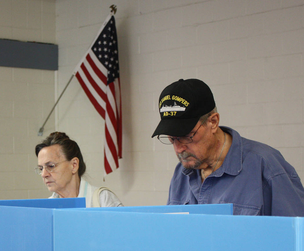 Robin Hebrock/Pahrump Valley Times Two voters are shown contemplating their choices while exercising their right to vote.