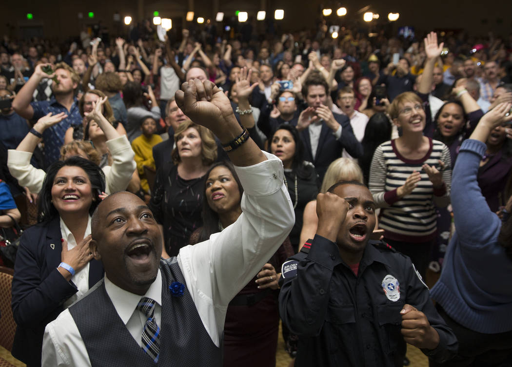 Benjamin Hager/Las Vegas Review-Journal Assemblyman Tyrone Thompson, left, cheers as results come in for Congresswoman Jacky Rosen during an election night event hosted by the Nevada Democrats on ...