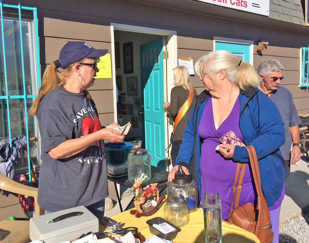 Robin Hebrock/Pahrump Valley Times A Tails of Nye County volunteer mans the cash box at the group's yard sale fundraiser, hosted Nov. 2 and 3.