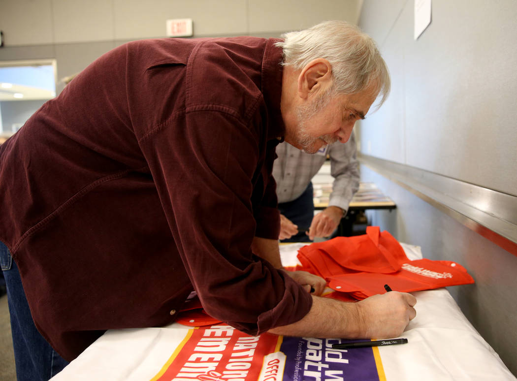 Cold War Patriot Art Goldberger of Las Vegas signs a banner during the Official National Day of Remembrance honoring all Nevada Test Site workers, their family members and friends at National Atom ...