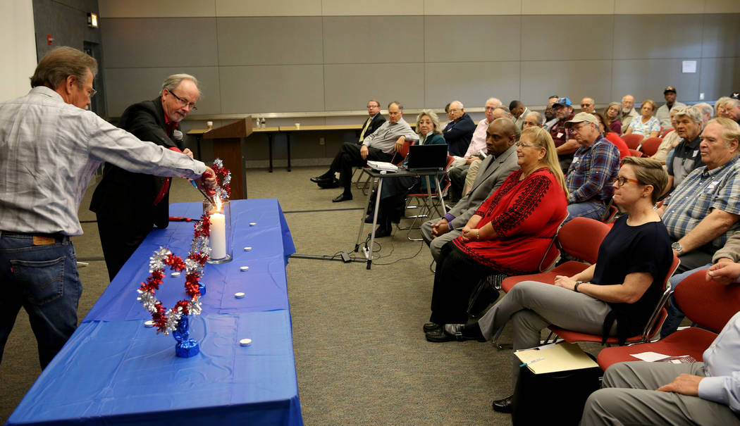 Randy Rhode of Las Vegas, a retired radiation technician, left, and Tim Lerew, chairman of Cold War Patriots, light the remembrance candle during the Official National Day of Remembrance honoring ...