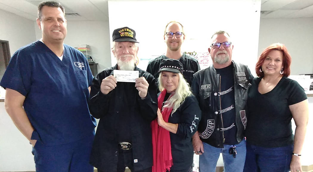 """Selwyn Harris/Pahrump Valley Times Tribe Motorcycle Club President Ralph """"Red"""" Pillman, holding a $500 check, is joined by his wife Joanna, along with Dr. Michael Taylor, left. Rounding out the gr ..."""