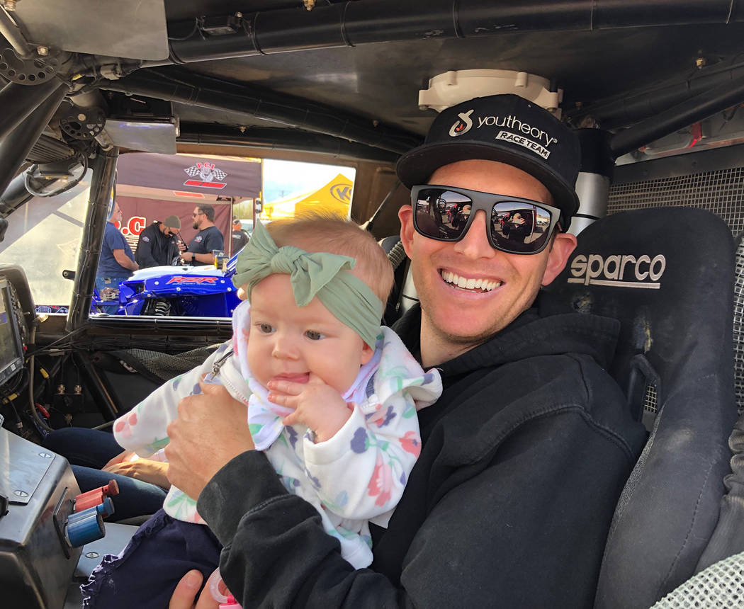 Tom Rysinski/Pahrump Valley Times Trick Truck driver Anthony Terzo of Irvine, California, sits Friday with his 6-month-old daughter Masyn while waiting for a technical inspection of his vehicle fo ...