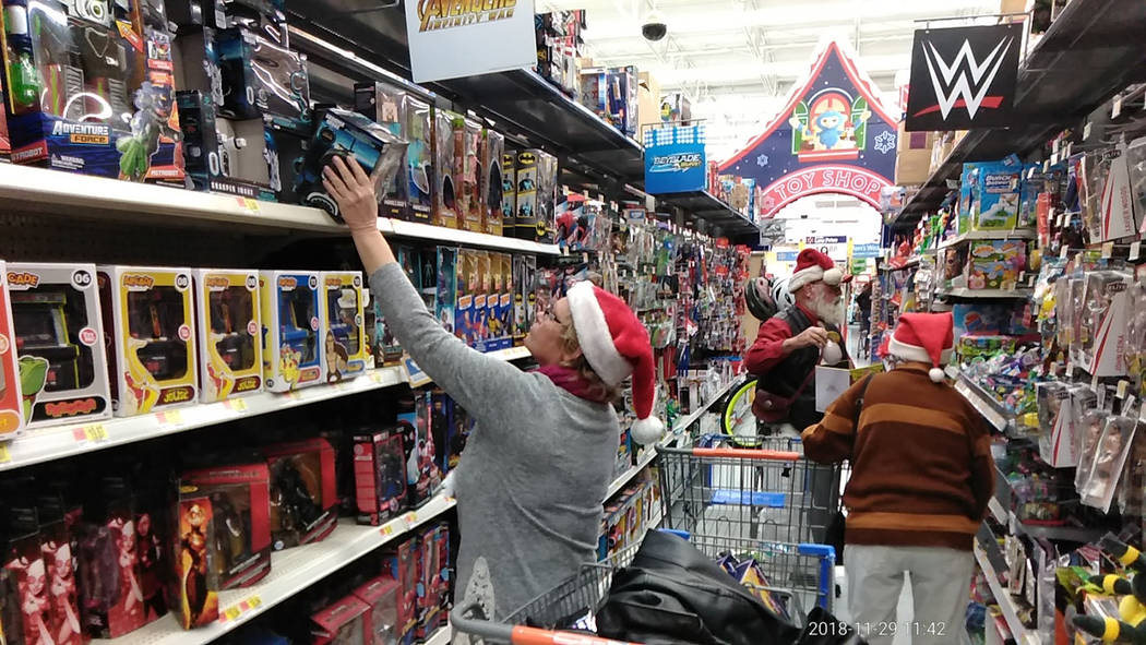 """Selwyn Harris/Pahrump Valley Times Fred """"Santa"""" Summers and his """"elves"""" check out the shelves of the toy section at Walmart. Summers said his aim is to provide a toy for every child in the Town of ..."""