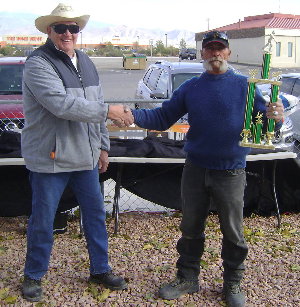 Mike Norton/Special to the Pahrump Valley Times Dennis Andersen presents the championship trophy to Dok Hembree after last year's inaugural Christmas Open horseshoes tournament in Pahrump.