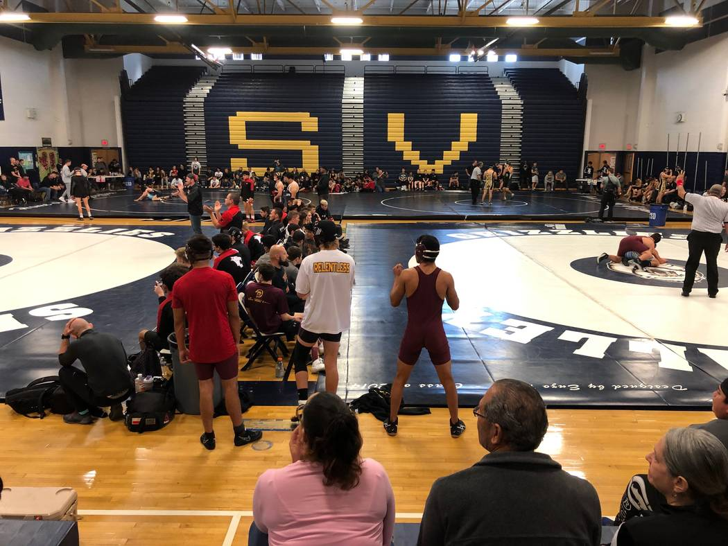 Tom Rysinski/Pahrump Valley Times Pahrump Valley wrestlers compete in the lower right while three other matches take place Saturday at the Spring Valley Duals. The Trojans went 4-1 in the event an ...