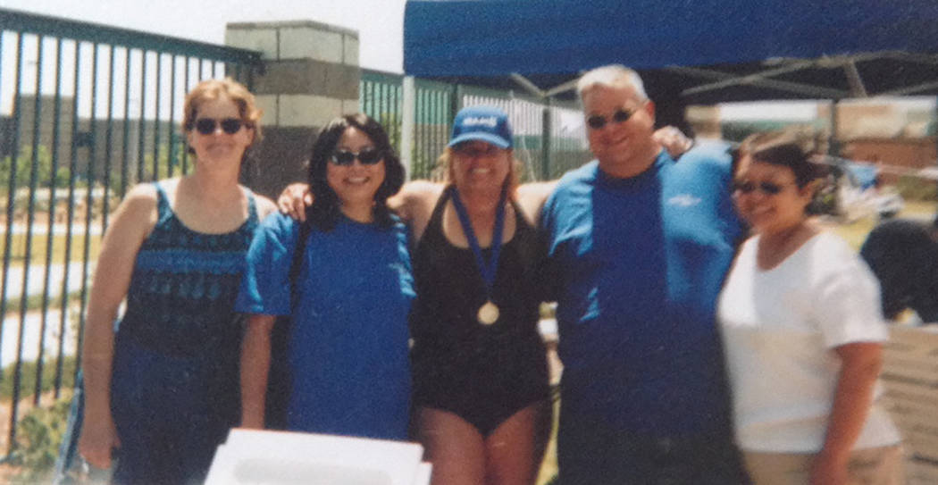Special to the Pahrump Valley Times Cathy Behrens, center, shows off her medal from the first competition she ever entered, a Corporate Challenge in 2001, surrounded by executives from Treasure Is ...