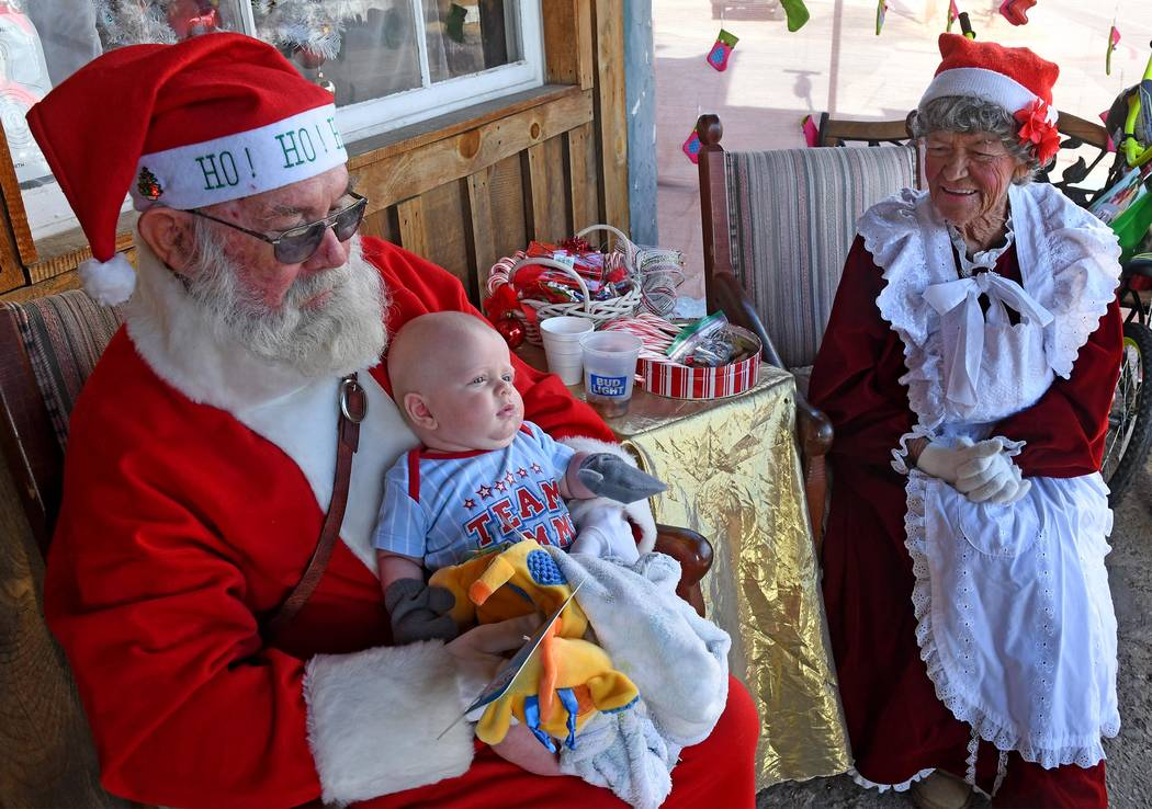 Richard Stephens/Special to the Pahrump Valley Times Fred and Patti Summers as Santa and Mrs. Claus, distribute toys in front of the Happy Burro in Beatty on Saturday, Dec. 8.