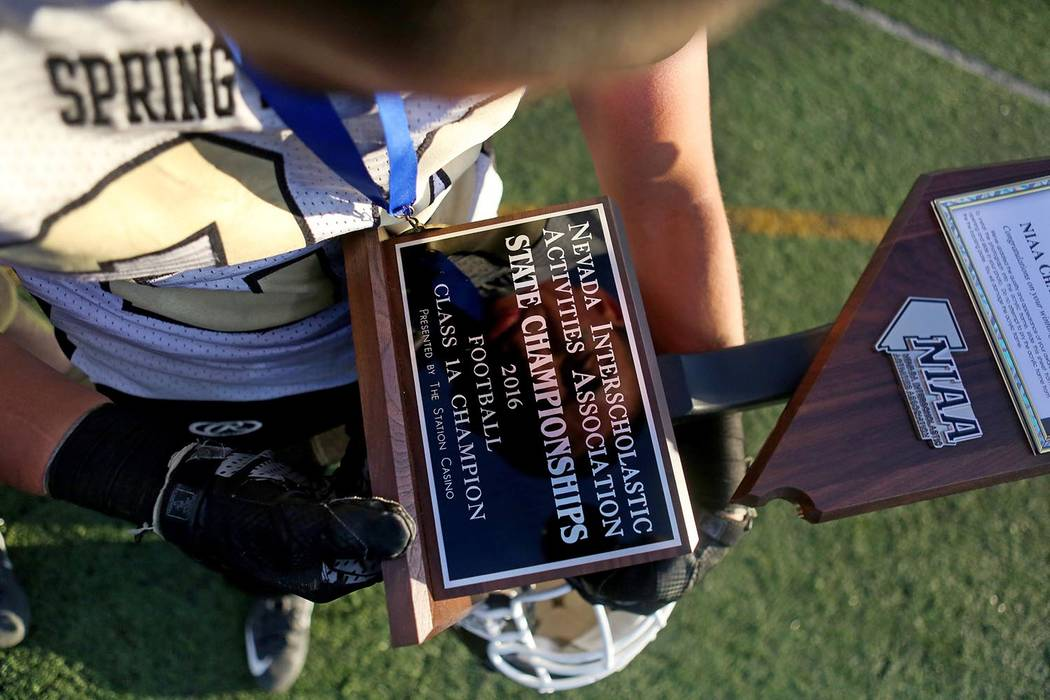 Elizabeth Page Brumley/Las Vegas Review-Journal A Spring Mountain football player holds the Class 1A state football championship trophy after the Golden Eagles defeated Pahranagat Valley on Nov. 1 ...