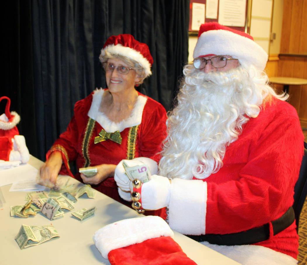 Robin Hebrock/Pahrump Valley Times Pam and Phil Raneri embodied Santa and Mrs. Claus. The two are shown counting up all of the additional donations given during the Nevada Silver Tapper's fundrais ...