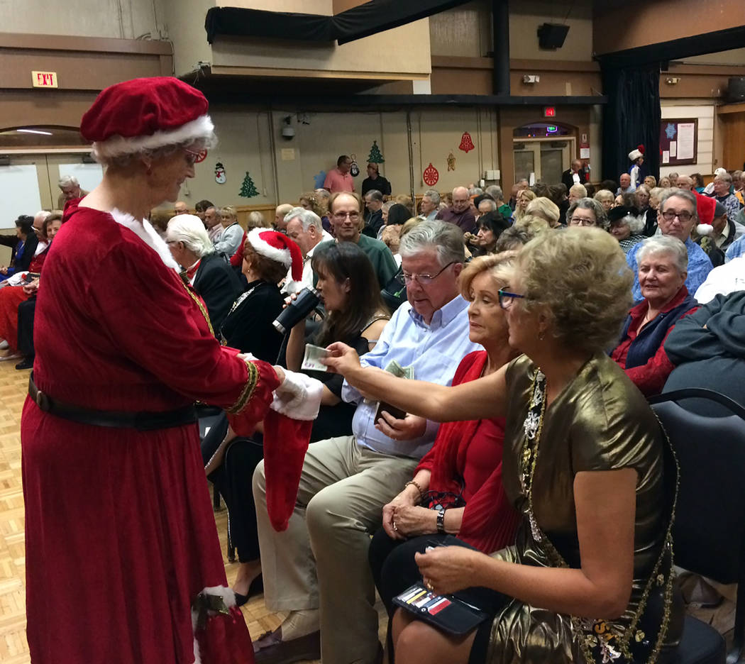 """Robin Hebrock/Pahrump Valley Times Pam Raneri, dressed as Mrs. Claus, helps raise even more money with the """"pass the stocking"""" donation gather, a traditional part of every Christmas Benefit Show."""