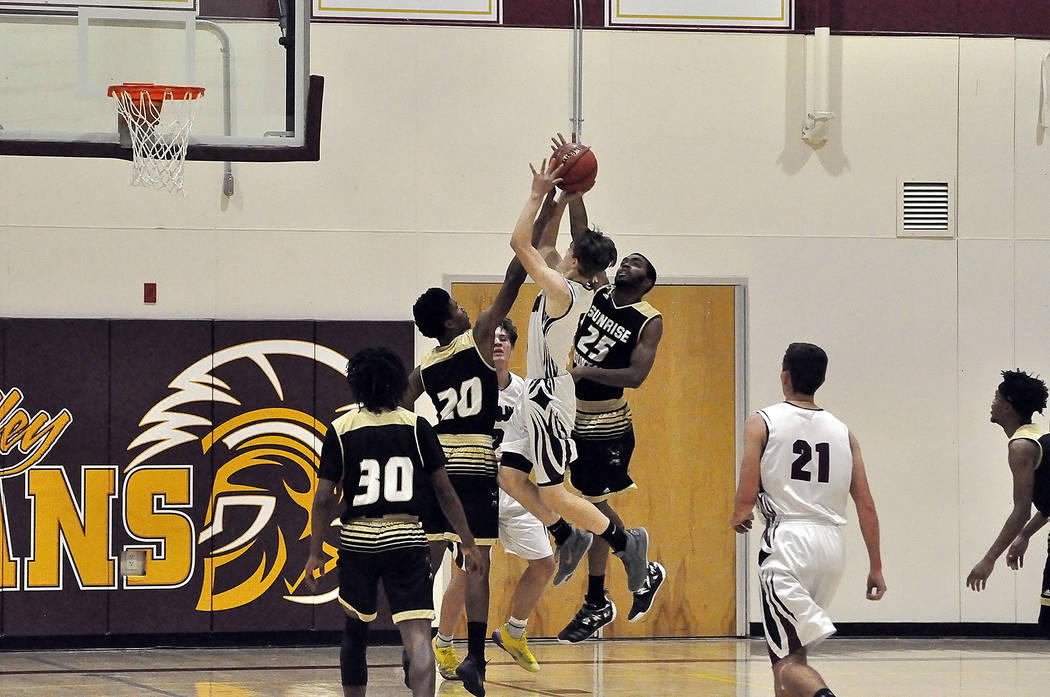 Horace Langford Jr./Pahrump Valley Times Pahrump Valley sophomore guard Logan Gavenda drives to the basket against Cy'Wan Joseph (20) and Jaylen Beatty (25) of Sunrise Mountain during Friday night ...