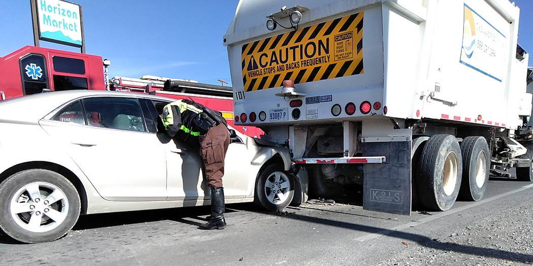 Selwyn Harris/Pahrump Valley Times A Nye County Sheriff's Office deputy inspects the interior of the sedan which rear-ended a sanitation truck late Wednesday morning along East Mesquite Avenue, ju ...
