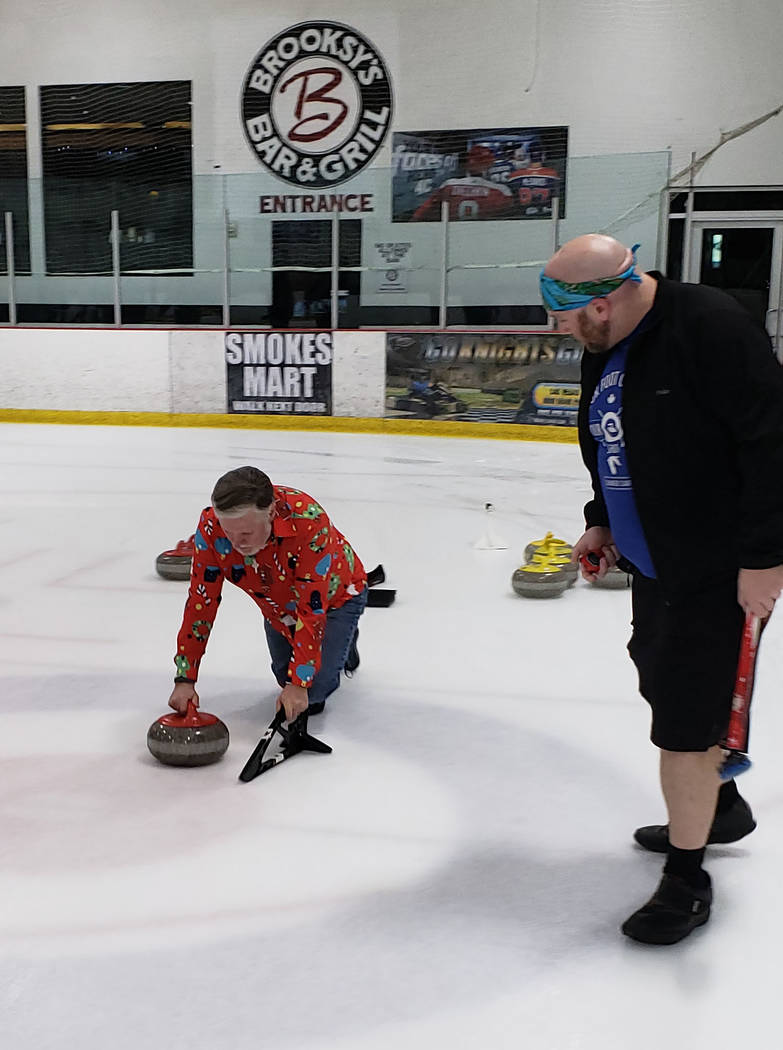 Karen Duryea/Special to the Pahrump Valley Times Pahrump resident Tom Duryea, left, throws the stone while Nolan Ehrstrom prepares to sweep during a recreational curling league at the Las Vegas Ic ...