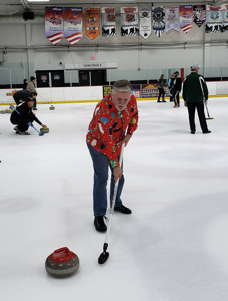 Karen Duryea/Special to the Pahrump Valley Times Tom Duryea of Pahrump sweeps to help guide the stone toward the house during the Las Vegas Curling Club's recreational league.