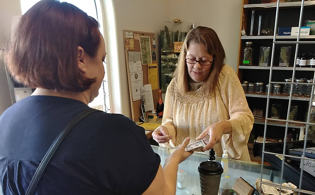 Selwyn Harris/Pahrump Valley Times All About Hemp's Andrea Nixon completes a transaction on Saturday morning during the business' grand opening event. Co-owner Jim McCoy said he was quite pleased ...