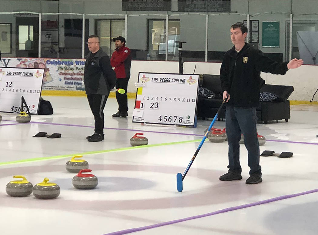 Tom Rysinski/Pahrump Valley Times Pahrump resident Matt Duryea signals a teammate where to throw the stone during a curling bonspiel Jan. 11 in Las Vegas.