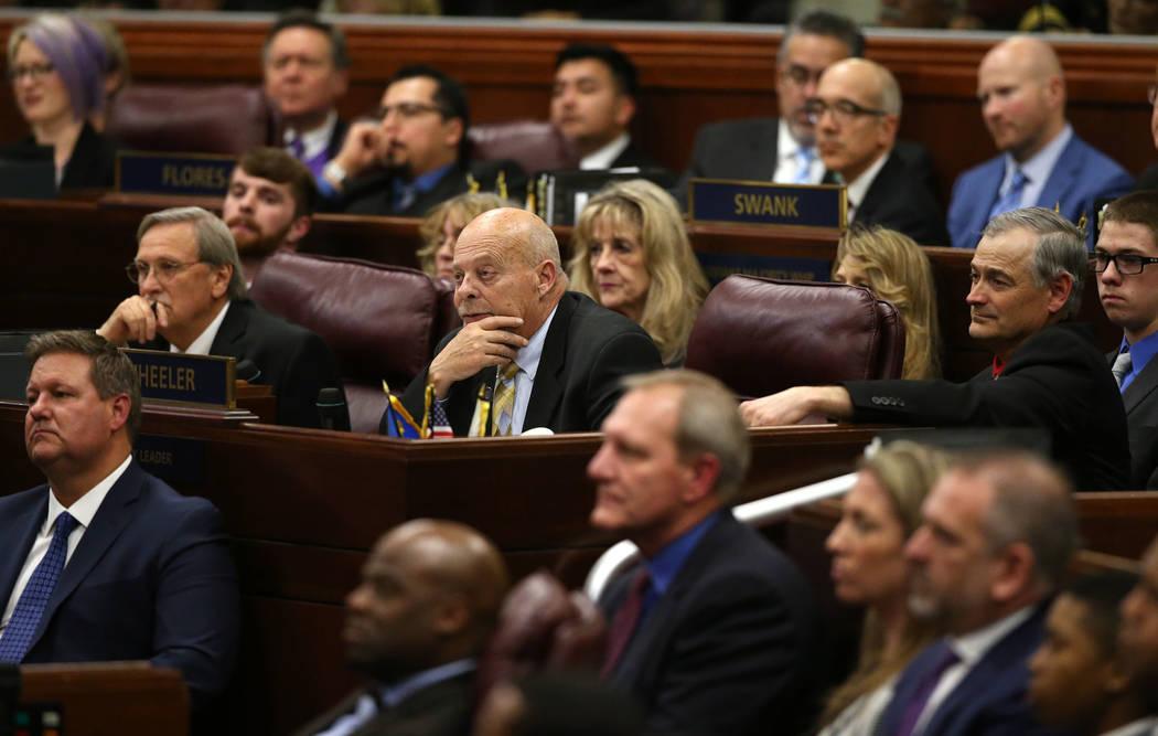 From left, Nevada Assemblymen John Ellison, R-Elko, Jim Wheeler, R-Gardnerville, and Senator James Settelmeyer, R-Gardnerville, listen as Gov. Steve Sisolak delivers his State of the State address ...